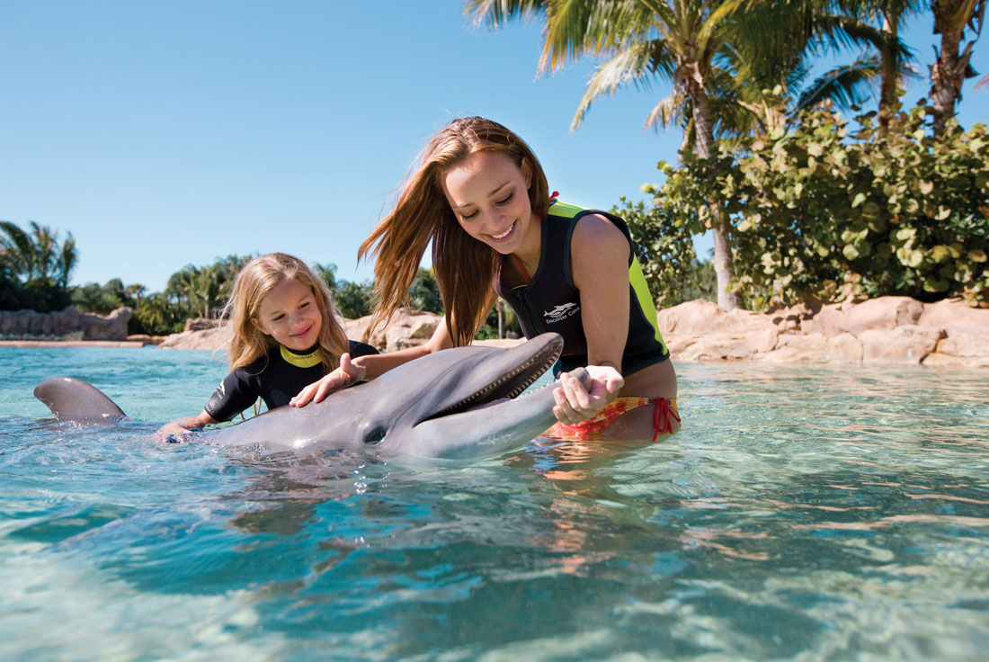 04discovery-cove-bottlenose-dolphin-with-Two-Girls